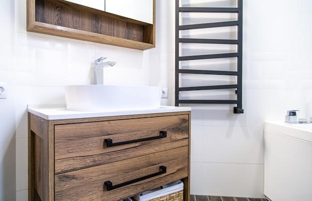Intérieur de salle de bain clair avec des meubles en bois dans un style minimaliste.