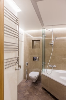 Intérieur d'une salle de bain combinée. douche et wc encastré dans la chambre décorée de carreaux de céramique imitant le marbre. il y a une douche sanitaire et un radiateur mural pour les serviettes.