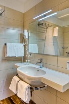 Intérieur de la salle de bain dans un style moderne minimaliste avec miroir, lavabo sur socle en pierre, serviettes, gel et carreaux de bois