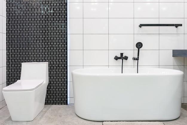 Intérieur de la salle de bain avec douche et éclairage minimalistes, toilettes blanches, lavabo et baignoire