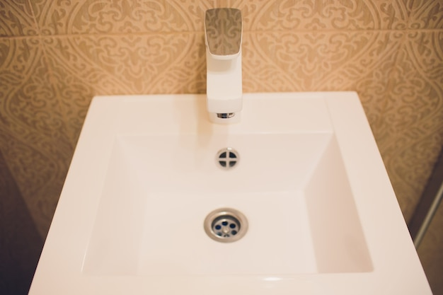 Intérieur de salle de bain avec lavabo et robinet blanc.