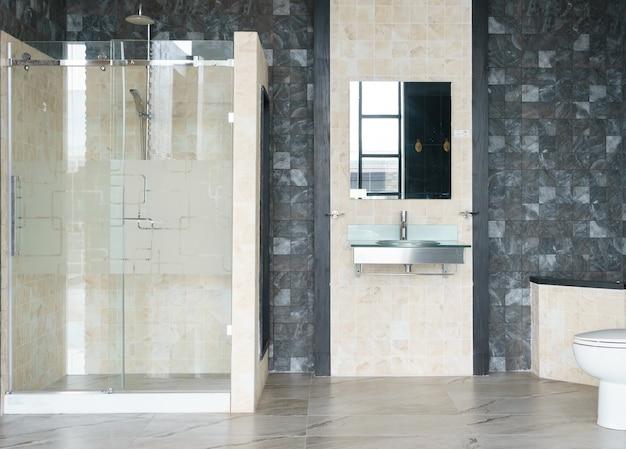 Intérieur de salle de bain avec des murs blancs, une cabine de douche avec mur de verre