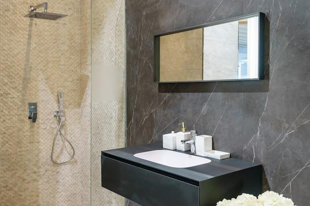 Intérieur de salle de bain avec des murs blancs, une cabine de douche avec paroi en verre, un lavabo de toilettes et de robinets