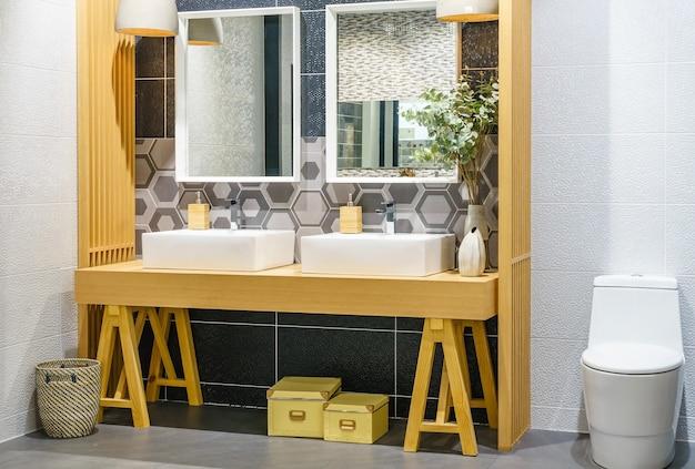 Intérieur de la salle de bains en carrelage blanc avec un double évier posé sur une étagère en bois et une douche.