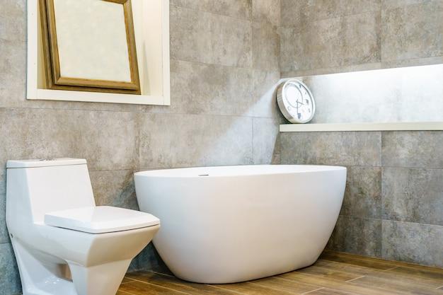 Intérieur d'une salle de bains contemporaine avec baignoire blanche, lavabos et toilettes