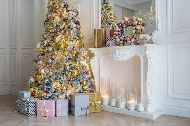 Intérieur de la salle blanche avec arbre du nouvel an décoré de boîtes à cadeaux et cheminée