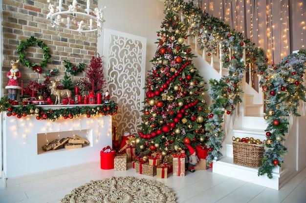 Intérieur de la salle blanche dans des tons rouges avec arbre du nouvel an décoré, boîtes à cadeaux et cheminée artificielle