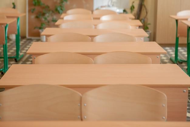 Intérieur de la salle de classe vide avec chaises et bureaux d'affilée