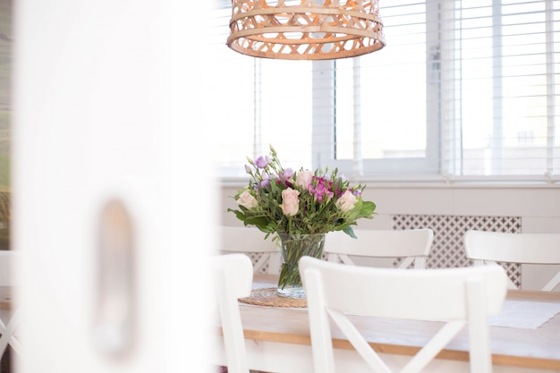 Intérieur de salle à manger confortable avec décoration florale dans une salle blanche d'un gros plan de maison moderne