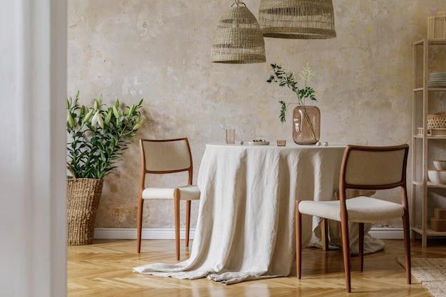 Intérieur de salle à manger élégant et élégant avec table à manger, chaises design, suspensions en rotin, fleurs séchées dans des vases, meubles, décoration et accessoires personnels élégants dans un décor chaleureux.