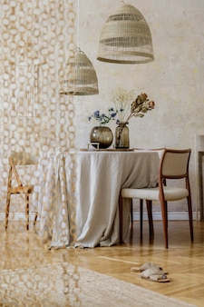 Intérieur de salle à manger élégant avec table en bois, chaises design, suspension en rotin, fleurs printanières dans un vase, belles assiettes, plantes et décoration élégante. concept de wabi sabi. modèle.