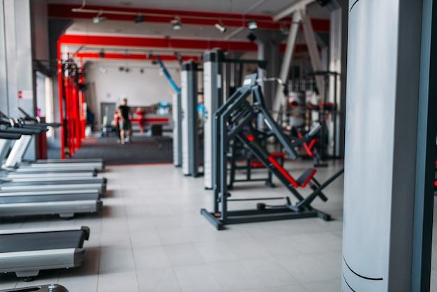 Intérieur de la salle de sport, personne, machines d'exercice et équipement sportif dans un club de remise en forme