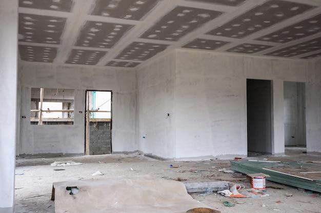 Intérieur de la salle vide avec plafond en plaques de plâtre au chantier de construction de la maison