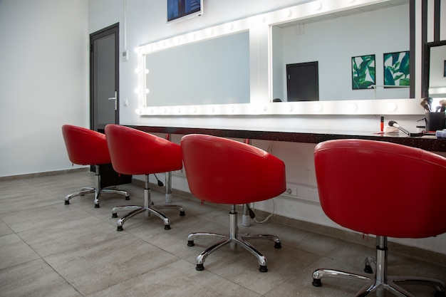 Intérieur d'un salon de beauté avec chaises rouges et miroirs