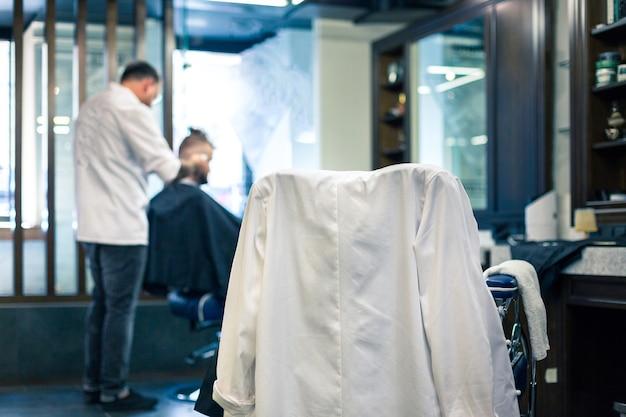 Intérieur de salon de coiffure de luxe, meubles chers bleus, garnitures en bois, plafond noir à la mode