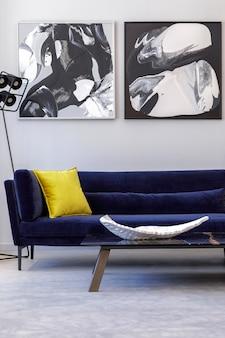 Intérieur de salon élégant et moderne avec canapé en velours bleu, peintures, mobilier design, plante, table, décoration, sol en béton, accessoires personnels élégants dans la décoration intérieure.