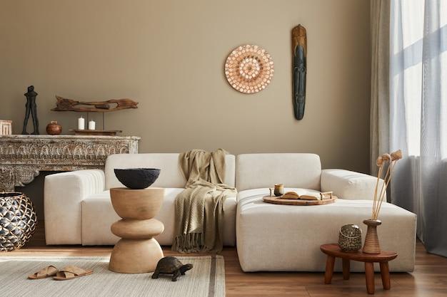 Intérieur de salon ethnique élégant avec canapé design, tabouret en bois, étagère marocaine, décor de tapis, un lof de décoration et d'élégants accessoires personnels.