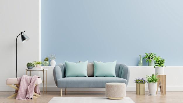 Intérieur d'un salon lumineux avec oreillers sur un canapé et un fauteuil, des plantes et une lampe sur un mur bleu vide
