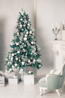 Intérieur de salon de luxe avec canapé décoré arbre de noël chic, cadeaux, plaid et oreillers.