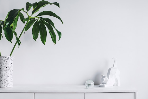 Intérieur de salon minimaliste créatif avec espace de copie feuille de commode moderne blanche dans un vase et sculpture de murs blancs template