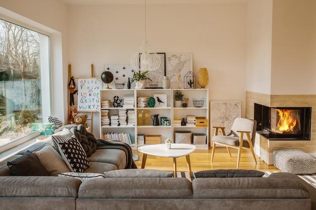 Intérieur de salon scandinave blanc avec cheminée, affiches, canapé d'angle et jouets pour enfants