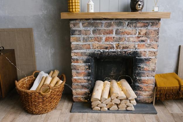 Intérieur scandinave avec cheminée en brique rouge, panier en osier pour le bois de chauffage, tas de bûches pour un feu