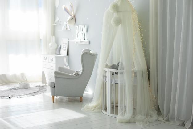 Intérieur scandinave élégant de la chambre de bébé nouveau-né avec fauteuil gris et berceau avec auvent blanc suspendu