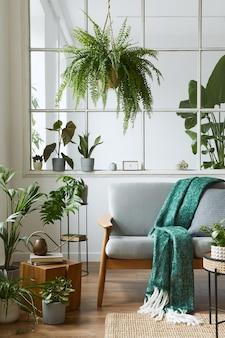 Intérieur scandinave moderne du salon avec canapé gris design, fauteuil, beaucoup de plantes, table basse, tapis et accessoires personnels dans une décoration chaleureuse. modèle.