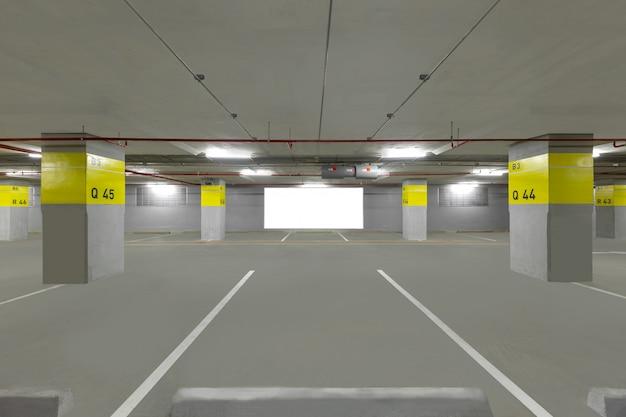 Intérieur souterrain de garage de stationnement avec panneau vierge.
