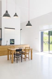 Intérieur spacieux d'une cuisine et salle à manger dans une maison contemporaine, avec murs, sol et plafond blancs