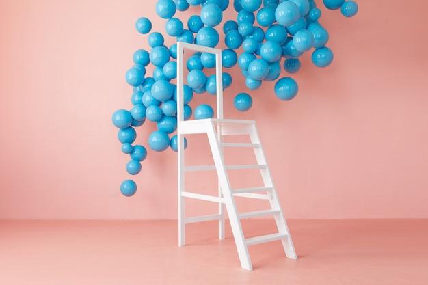 Intérieur de studio lumineux rose avec échelle blanche et balles bleues suspendues.