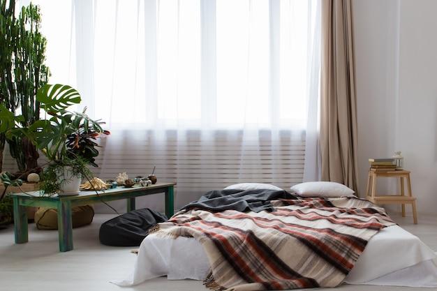 Intérieur d'un studio moderne avec beaucoup de plantes et un lit à l'étage