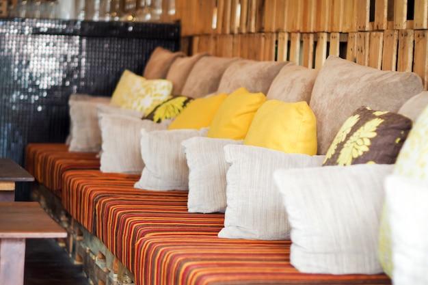Intérieur de style moderne avec un tapis au sol. il y a un canapé avec des oreillers et ca