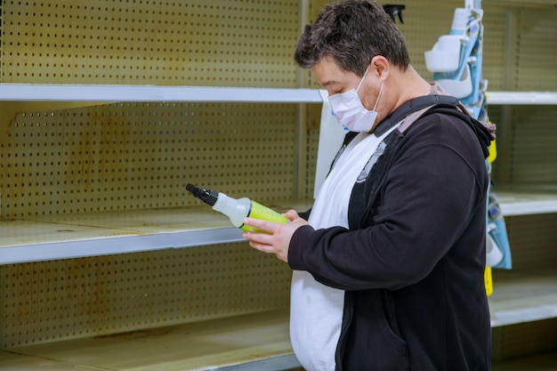 Intérieur de supermarché avec masque de protection médicale homme choisissant en magasin avec des étagères vides pendant le coronavirus
