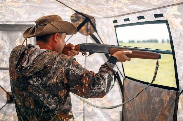 L'intérieur de la tente des chasseurs, l'homme dans un chapeau de camouflage et de cow-boy debout avec le fusil et visant à partir du concept de buteur de fenêtre