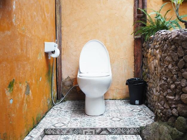 Intérieur des toilettes avec cuvette blanche.