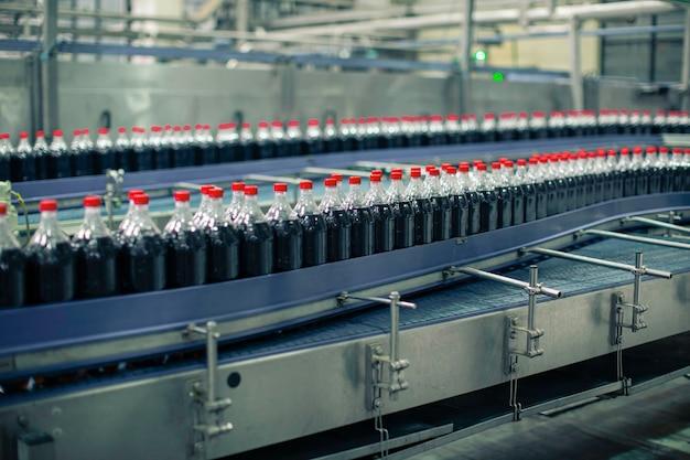Intérieur de l'usine de boissons. convoyeur circulant avec des bouteilles d'eau gazeuse.