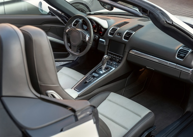 Intérieur de voiture décapotable de luxe, vue depuis la porte des passagers. intérieur cabriolet de voiture de sport avec sièges blancs et tableau de bord noir