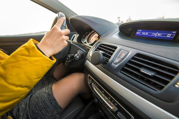 Intérieur de voiture moderne avec chauffeur femme mains sur volant. concept de conduite sûre.