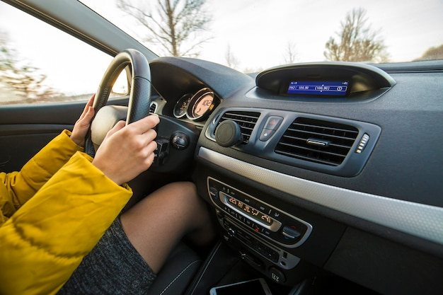 Intérieur de voiture moderne avec des mains féminines de conducteur sur le volant. concept de conduite sûre.