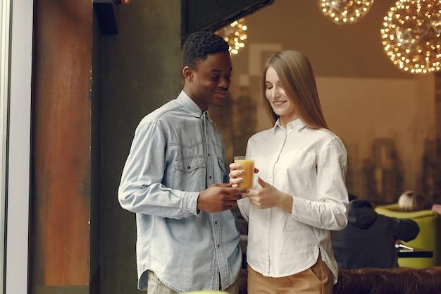 Internationals personnes debout dans un café avec du jus d'orange