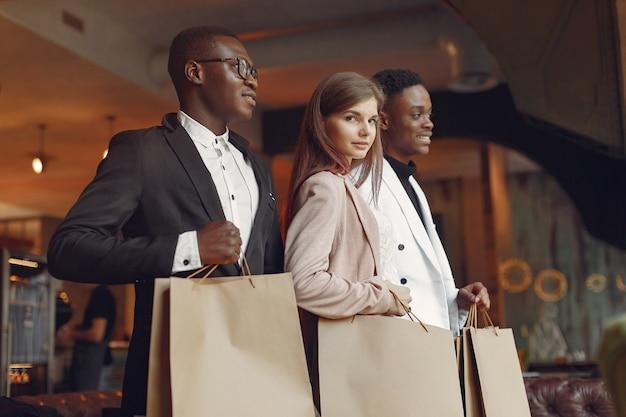 Internationals personnes debout dans un café avec des sacs à provisions