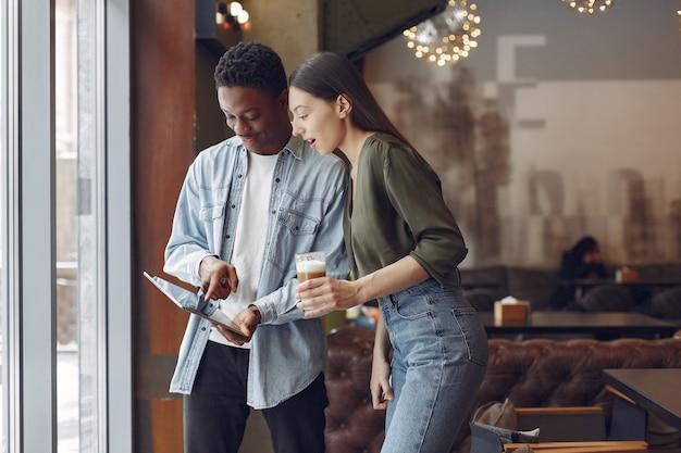 Internationals personnes debout dans un café avec tablette et café