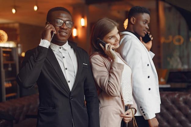 Internationals personnes debout dans un café avec téléphone portable