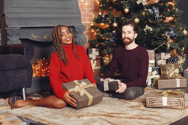 Les internautes à la maison. couple dans une décoration de noël. femme africaine et homme caucasien.
