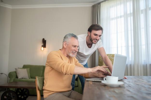 Sur internet. deux hommes dans la chambre à l'ordinateur portable regardant quelque chose sur un ordinateur portable