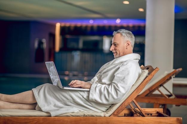 Sur internet. un homme barbu aux cheveux gris dans un peignoir blanc passe du temps sur internet