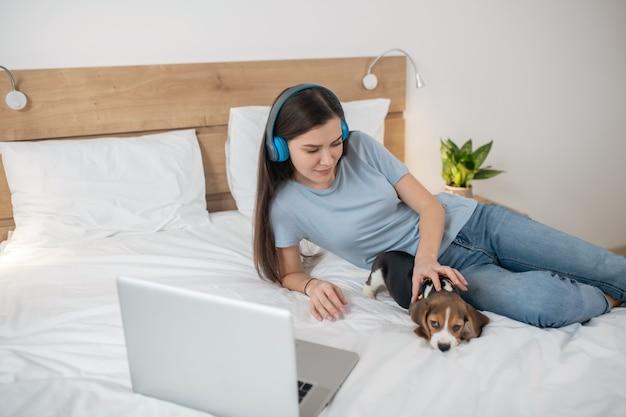 Sur internet. jeune femme brune écoutant de la musique et passant du temps en ligne