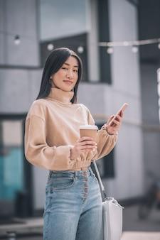 Sur internet. jolie jeune femme asiatique tenant un smartphone dans ses mains