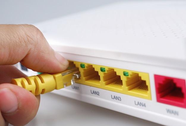 Internet modem routeur hub avec main tenant un câble jaune reliant isolé fond blanc